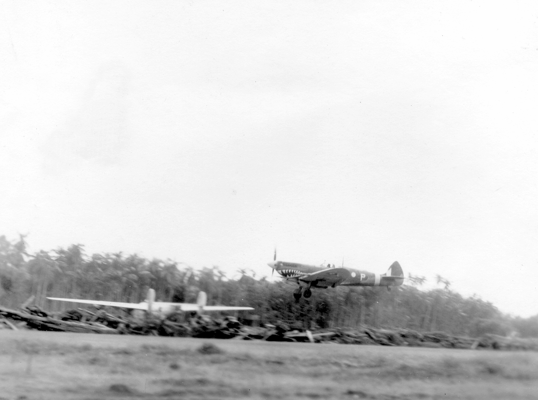 No. 457 Sqn Spitfire coasts down for landing. B-24 Liberator in the background.