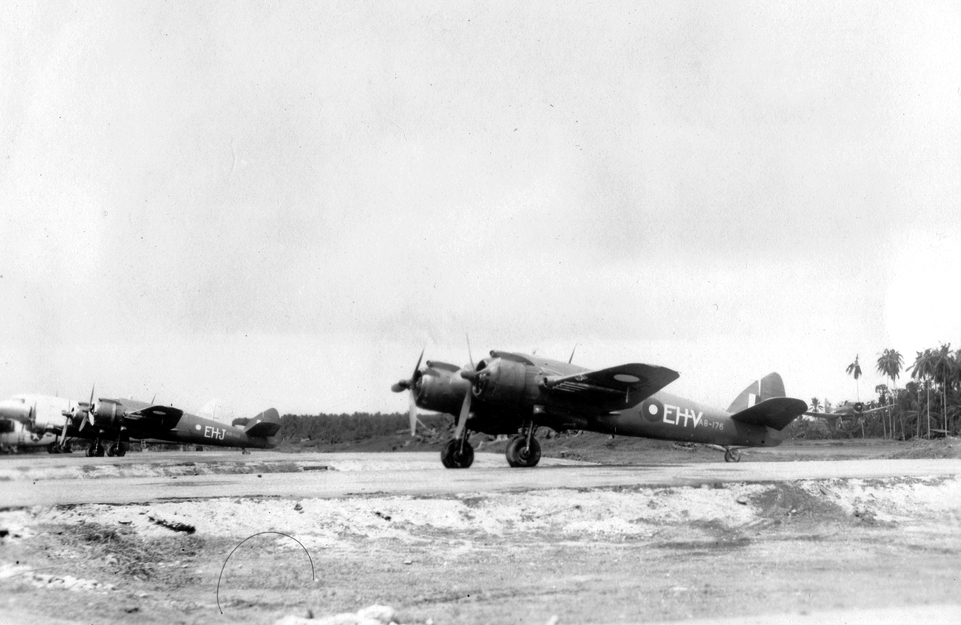 A pair of Beaufighters from No. 31 Squadron await their next mission (A8-143 in background, A8-176 in the fore). Note the Dauntless swooping down from the right.