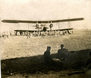 From the shade of the hangar, French pilots take a look at an RFC Handley Page 0/400.