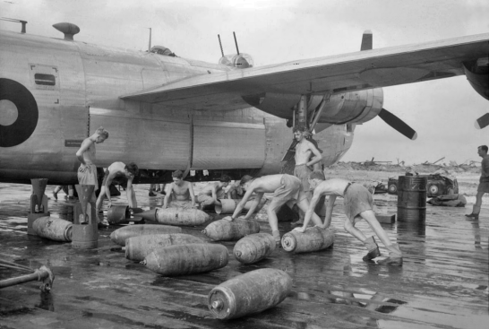 Armourers of 356 Sqn prep their bombs on the rain-drenched hardstand.