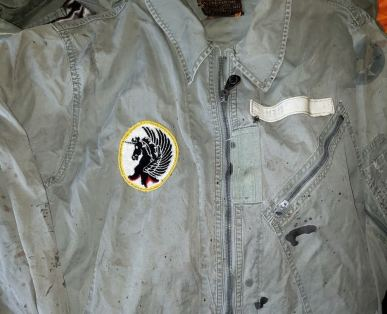 "This patch design of the 2nd Fighter Interceptor Squadron is always attributed to its later years as a training squadron in the mid-1970s. Fine, but what is it doing on a flightsuit from the early 1950s? This is the first pattern of K-2B flightsuit: big collar, only one chest pocket. The nametape is certainly of the era, not the 70s. It and the patch were sewn on by the same man at the same time - a long time ago (the thread and stitching show that). Anything is possible, and one should be conservative in their judgement on such matters, but one also has a hard time believing that when the squadron reactivated in 1974 one of its pilots dusted off a 20 year old flightsuit and said ""make sure you sew on my outdated nametape at the same time""."