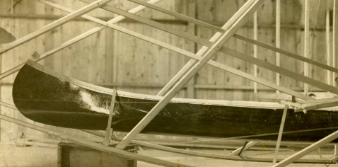 """A detailed shot of Wilbur's canoe. With an American flag fluttering in its bow, this vessel won the distinction as the """"World's first flying canoe""""."""