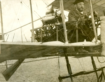 Farman at the controls of the Henri Farman n°1. Notice the spring shock absorbers. (Also, if you see a photo of Farman, he almost always has a cigarette at the ready)